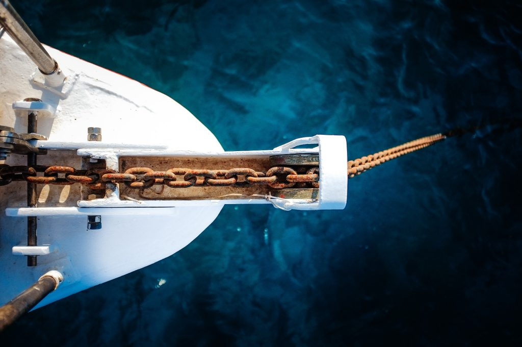 Our Riddle is about an anchor. This image is of a boat with it's anchor in the water.